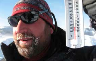 Paul Brown smiles with frost covered beard and sunglasses askew with the temperature at minus 35 degrees