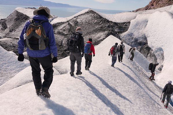 Don crampons for a trek on the Viedma Glacier, the largest in Los Glaciares National Park. Walk atop the ice to safely examine crevasses and caves below the glacier's rugged surface. ©Eric Rock
