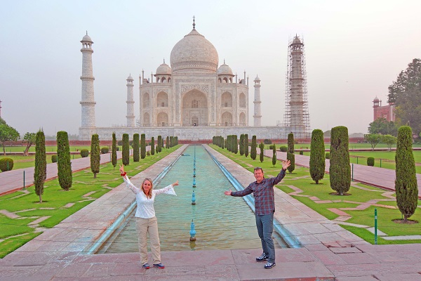 A couple posing at a crowd-free Taj Mahal in India
