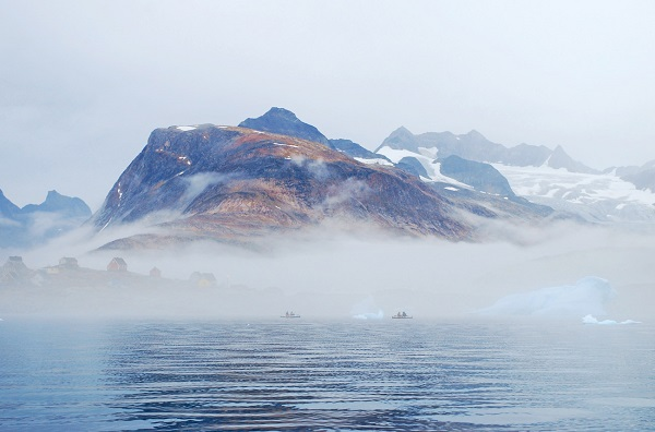Thick fog shrouds kayakers and icebergs alike near the tiny village of Tinit in eastern Greenland. Natural Habitat's Base Camp Greenland is located across the bay.