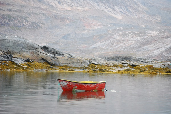 A cloudy day near Tinit made this boat's weathered coat of cheery red paint pop.