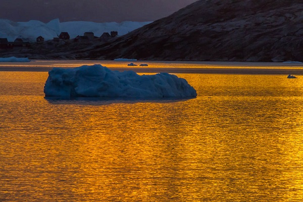 Sun sets on an iceberg in East Greenland