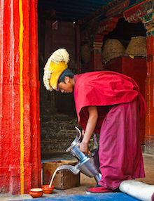 Monk in Tibet pouring butter tea