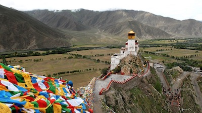 Tibet Monastery with Prayer Flags in the Mountains