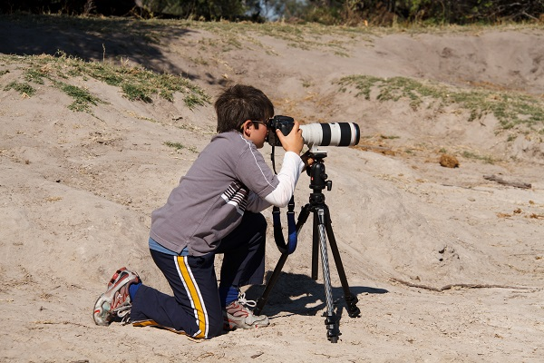 Boy on african safari looking in telescope.