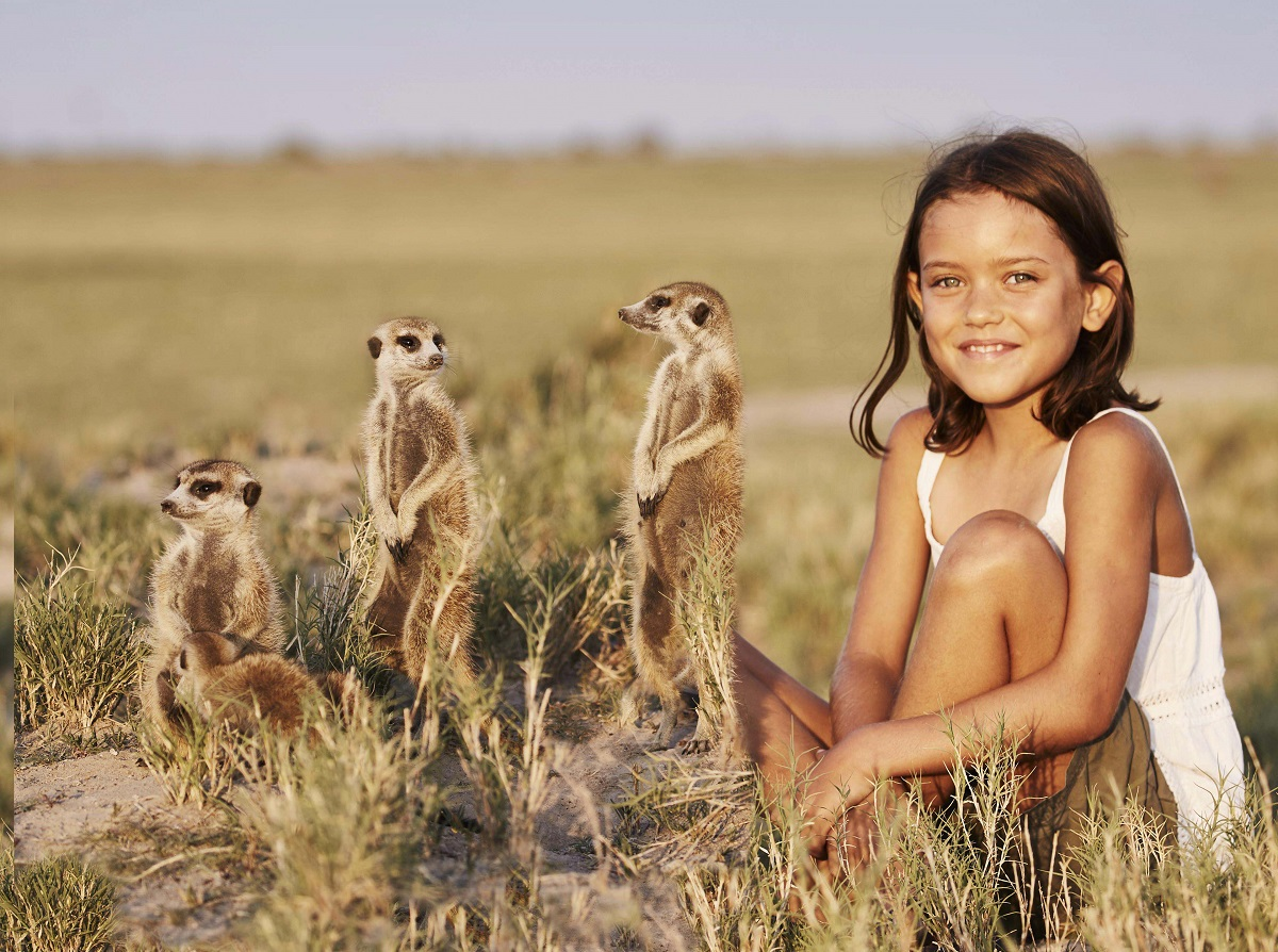 Girl with meerkats in Africa.