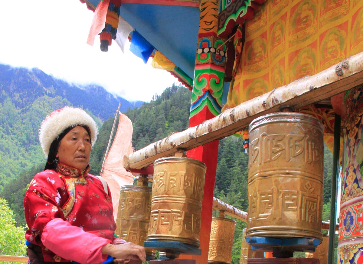 A women with prayer wheels at a traditional village in China.