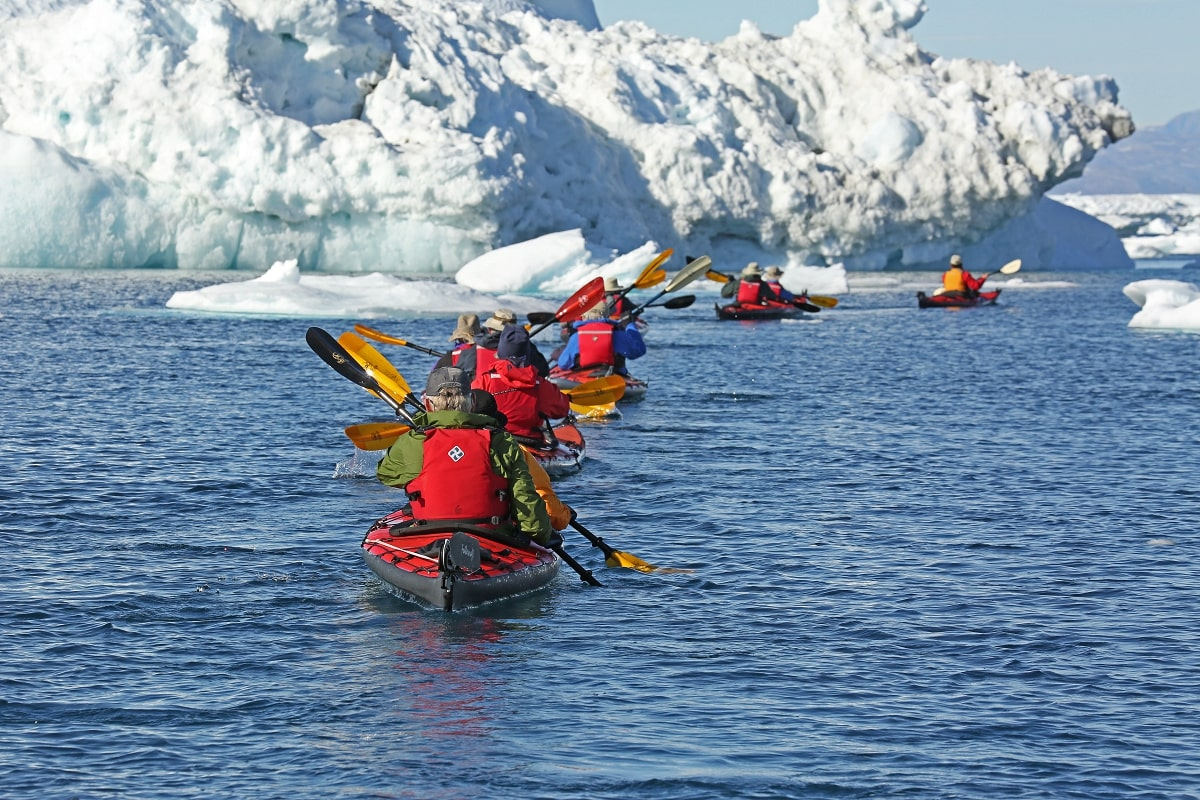 Kayakers pass icebergs in Greenland.