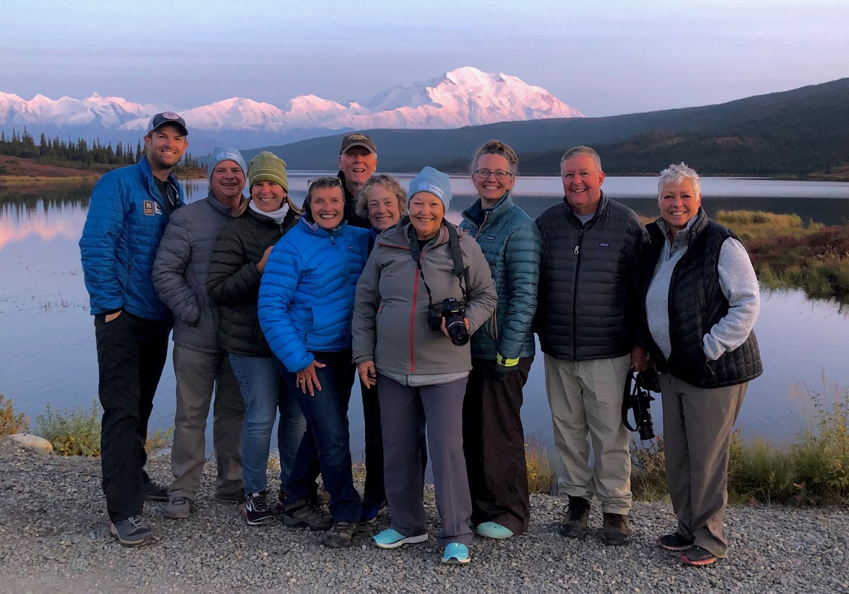Nat Hab travelers pose in front of Denali.