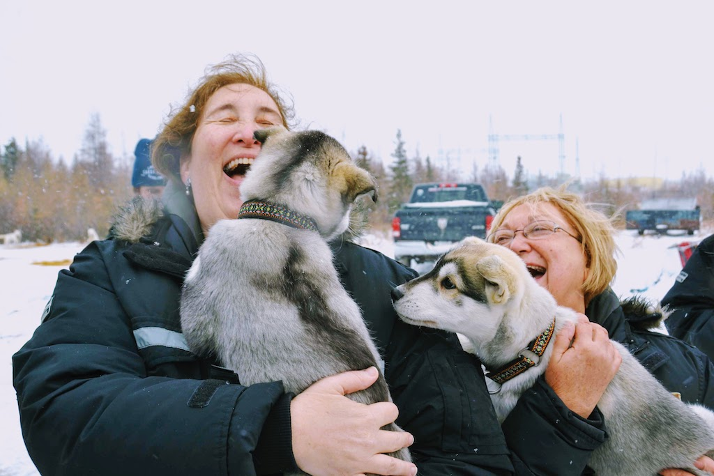 Nat Hab travelers snuggle with husky puppies before dogsledding in Churchill.